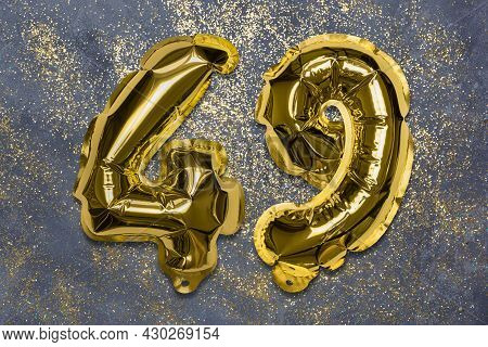 The Number Of The Balloon Made Of Golden Foil, The Number Forty-nine On A Gray Background With Sequi
