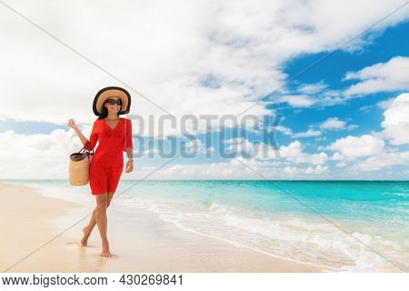 Luxury beach travel vacation elegant lady walking relaxing on holidays with beachwear accessories sunglasses, sun hat and bag wearing red cover-up dress.