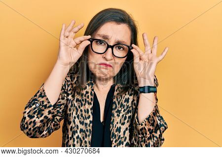 Middle age hispanic woman wearing business clothes and holding glasses depressed and worry for distress, crying angry and afraid. sad expression.