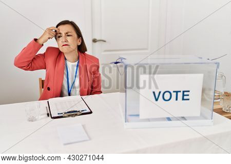 Beautiful middle age hispanic woman at political election sitting by ballot pointing unhappy to pimple on forehead, ugly infection of blackhead. acne and skin problem