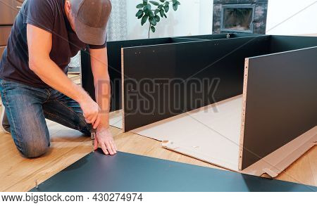 Furniture Assembly Workflow. A Man Collects Furniture Brought From The Store. Assembling The Cabinet
