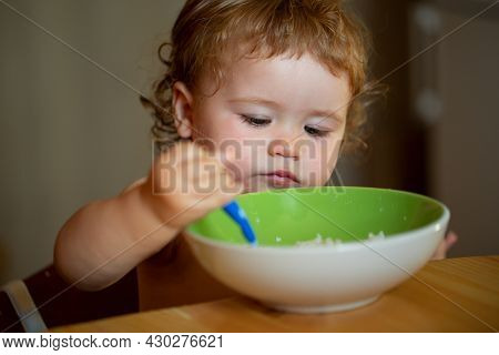 Happy Baby Eating Himself With A Spoon. Child Nutrition Concept.