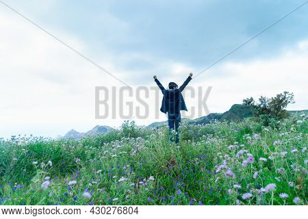 Rear View Of Young Man Hiker Traveler Standing On Dirt Mountain Path In Nature Reserve On Green Prai