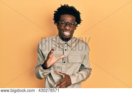 Young african american man wearing casual clothes and glasses disgusted expression, displeased and fearful doing disgust face because aversion reaction. with hands raised