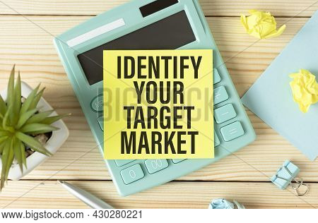 Notepad With The Text Identify Your Target Market On An Office Table With Pencils, Paper Clips And A