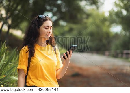 Portrait Of A Young Smiling Woman Typing On A Smartphone. Internet Addiction Concept. Tropical Park