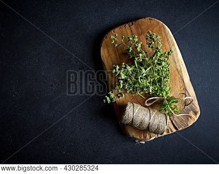Fresh Marjoram and kitchen twine on wooden board