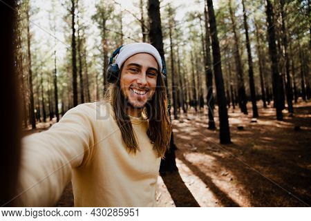 Handsome Caucasian Photographer Taking Selfie Wearing Beanie And Headphones Standing In Luscious For