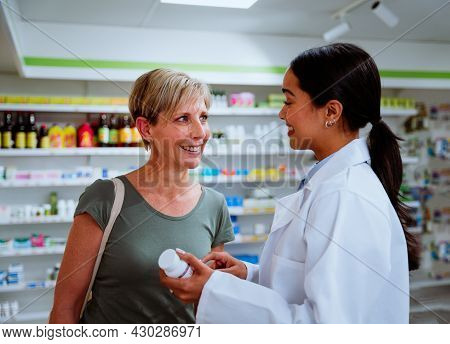 Middle-aged Mother Getting Assistant By Mixed Race Female Intern Helping Prescribe Medication