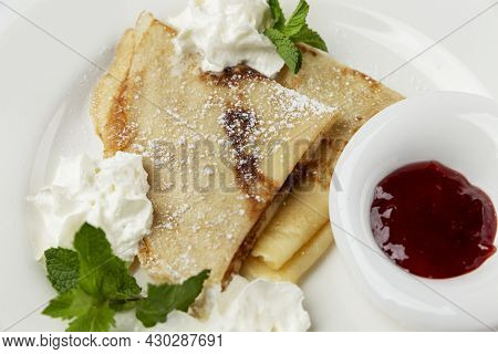 Pancakes With Cream, Mint And Berry Sauce On A White Plate. Traditional European Breakfast. Close-up