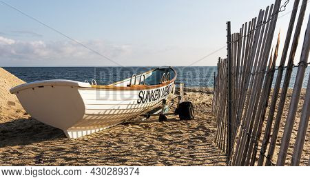 Kings Park, New York, Usa - 30 July 2021: White Lifeguards Row Boat On The Sand Next To A Fence At S