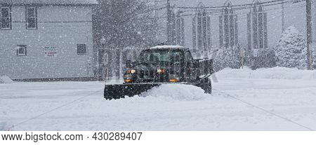 Babylon, New York, Usa - 1 February 2021: Black Truck With A Snowplow Clearing A Parking Lot Behind