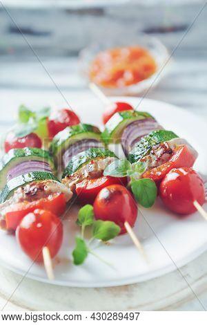 Grilled Shashliks With Vegetables And Pork Tenderloin. Bright Wooden Background. Close Up.
