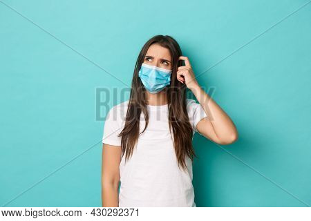 Concept Of Pandemic, Covid-19 And Social Distancing. Image Of Puzzled Young Woman In White T-shirt A