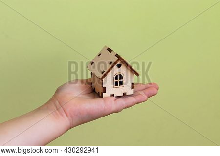 A Small House Made Of Wood In A Child's Palm. Real Estate Concept. Buying And Selling Houses. The Ho