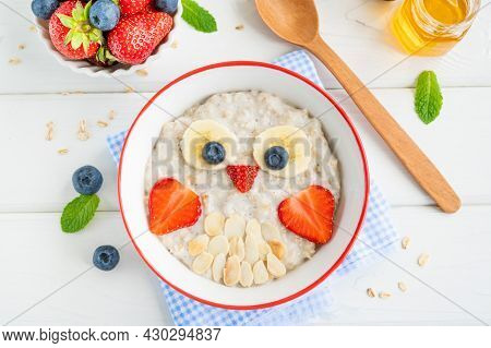 Funny Bowl With Oat Porridge With Owl Faces Made Of Fruits And Berries On A White Wooden Background.