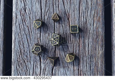 Overhead Image Of A Set Of Metallic Role-playing Dice On A Wooden Surface.
