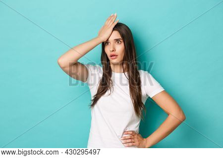 Young Annoyed Woman Slap Her Forehead And Standing Bothered By Something Stupid, Posing Over Blue Ba