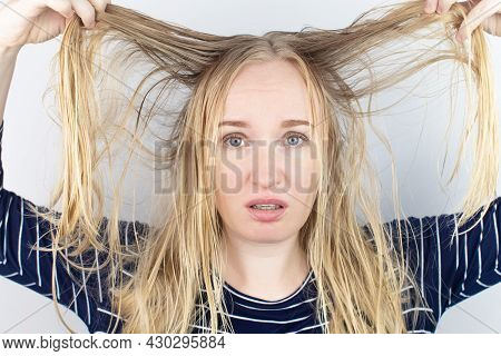The Girl Looks In Front Of The Mirror At Her Oily Hair. Problematic Scalp And Increased Secretion Of