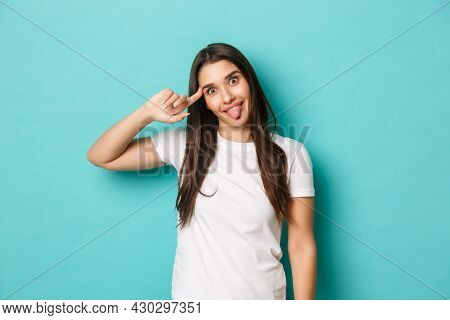Image Of Funny Cute Girl In White T-shirt, Mocking Someone, Pointing At Head And Showing Tongue, Act