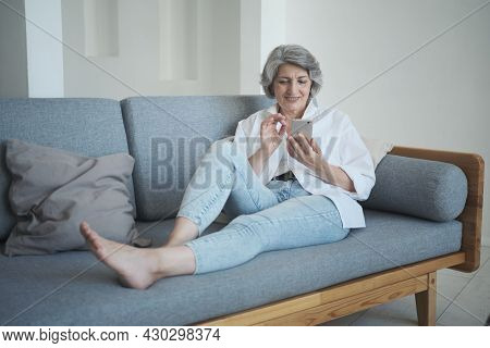 Smiling 60s Older Senior Middle-aged Adult Lady Enjoying Mobile For Video Conference Calling