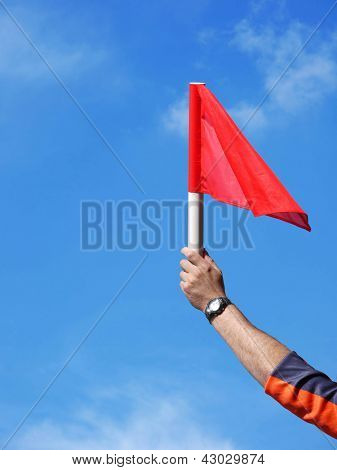 Soccer assistant referee hand holding up his red flag over blue sky signaling offside