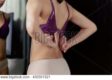 Shot In Low Light Woman Unhooking Her Bra And Looking In The Mirror Indoors.