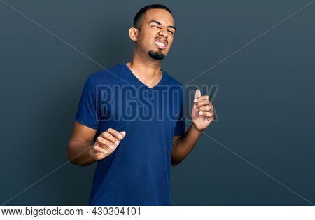 Young african american man wearing casual t shirt disgusted expression, displeased and fearful doing disgust face because aversion reaction. with hands raised