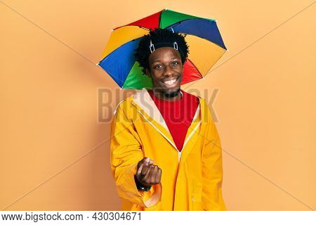Young african american man wearing yellow raincoat beckoning come here gesture with hand inviting welcoming happy and smiling