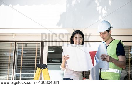 Asian Attractive Woman And Male Engineer, Looking At A Blueprint To Discuss About Renovating The Old