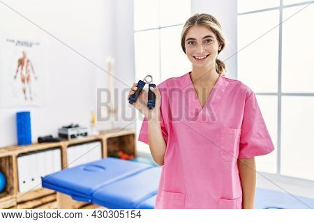 Young blonde woman working at pain recovery clinic holding hand strengthener looking positive and happy standing and smiling with a confident smile showing teeth