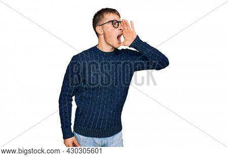 Young blond man wearing casual clothes and glasses shouting and screaming loud to side with hand on mouth. communication concept.