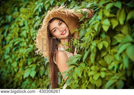 Charming young woman poses and smiles in a summer light dress and straw hat against the background of a green hedge in the park. Summer fashion and beauty.