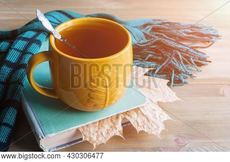 Autumn still life. Cup of tea, worn book with dry maple autumn leaf with green scarf on the wooden background. Autumn background,autumn composition, autumn still life, autumn indoors, autumn background, autumn concept