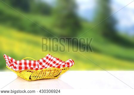 Empty Basket With Red Checkered Napkin On White Table Over Abstract Blurred Natural Sunny Landscape