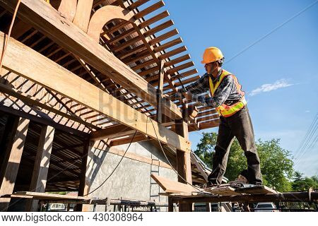 A Male Roofer Carpenter Working On Roof Structure On Construction Site