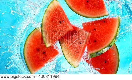 Fresh piece of water melons falling in water with splash on blue background