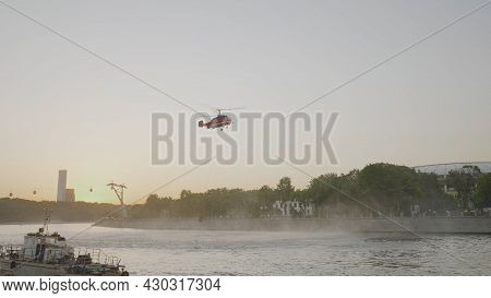 Rescue Helicopter Over City. Action. Helicopter Flies Over City Canal On Background Of Sunset. Rescu