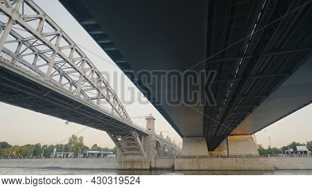 Sailing Under City Bridge Over Canal. Action. Sailing By Boat Under Big Bridge On City Canal. Highwa