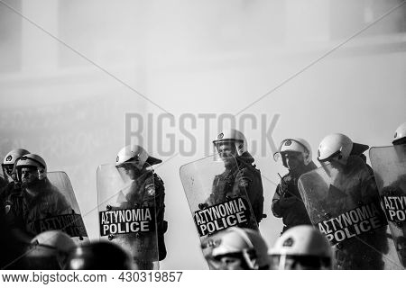 ATHENS, GREECE - APRIL 15, 2015: Riot police and protesters during a protest in front of Athens University, which is under occupation by protesters leftist and anarchist groups. Black-and-white photo.