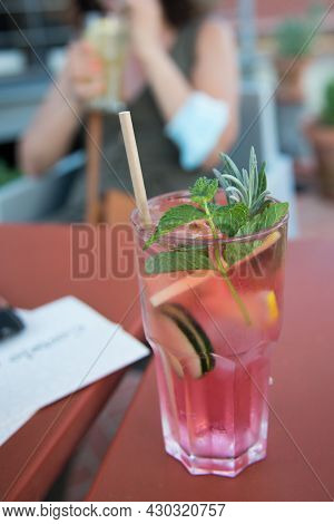 Cucumber Water With Berries And Lemon Slice, With Pink Colour And A Cardboard Straw. Woman In The Ba