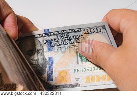 Business Man Count Money A Pile Of Hundred Stack Us Dollar Usd, Pay, Exchange And Looking At Numbers