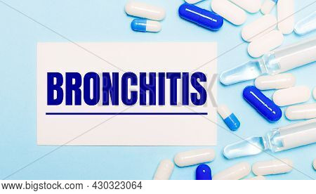 Ills, Ampoules And A White Card With The Text Bronchitis On A Light Blue Background. Medical Concept
