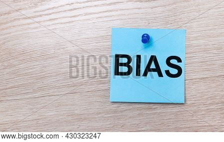 On A Light Wooden Background - A Light Blue Square Sticker With The Text Bias