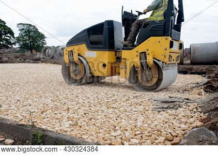 Drum Ride On Roller Compacting Freshly Laid Tarmac During Roadworks And New Footpath Construction