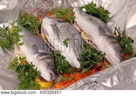 Fresh Raw Sea Bass And Sea Bream Ready For Baking With Carrots, Lemon, Red Onion, Garlic, Parsley An