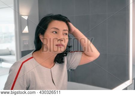 Hair loss mature Asian woman touching her hair styling or coloring gray hair looking at herself in home mirror. Beautifiul chinese professional lady makeup.