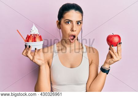 Young hispanic woman wearing sportswear holding apple and ice cream afraid and shocked with surprise and amazed expression, fear and excited face.