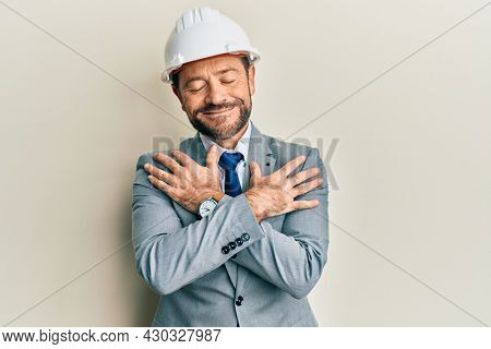 Middle age man wearing architect hardhat hugging oneself happy and positive, smiling confident. self love and self care
