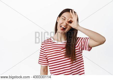 Positive Brunette Girl Shows Tongue, Okay Ok Sign Over Eye, Winking And Smiling Carefree, Enjoying E